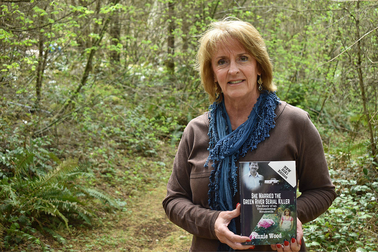 """Penny Wood holds a copy of her book """"She Married The Green River Serial Killer"""" on a trail near her Ravensdale home April 28. Photo by Alex Bruell"""